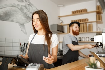 Coffee Business Concept - Beautiful female barista giving payment service for customer with credit card and smiling while working at the bar counter in modern coffee shop.
