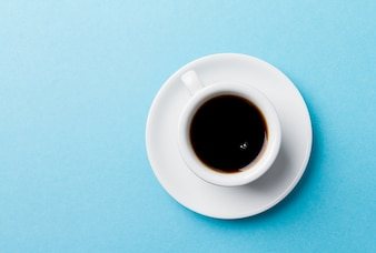 Coffee classic espresso in small white ceramic cup on blue vibrant background.