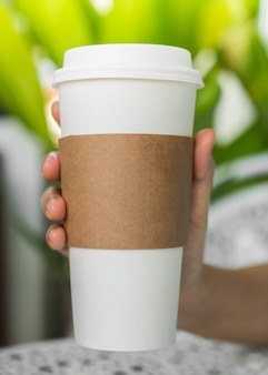 Coffee cup with cardboard to catch it