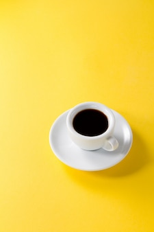 コーヒーのエスプレッソは、小さな白いセラミックのカップで黄色の活気のある背景に
