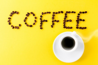 Coffee espresso in small white ceramic cup with coffee beans and word Coffee on yellow vibrant background. Minimalism Food Morning Energy Concept.