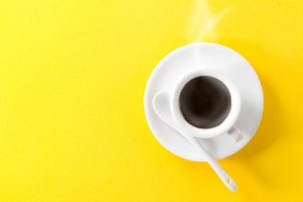 Coffee espresso in small white ceramic hot steam cup on yellow vibrant background. Minimalism Food Morning Energy Concept.