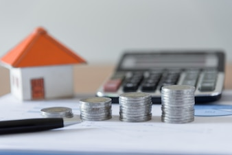 Coins stack with pen, paper house and calculator on business document chart office desk backgrounds