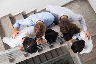 Colleagues Embracing and Looking down Stairwell