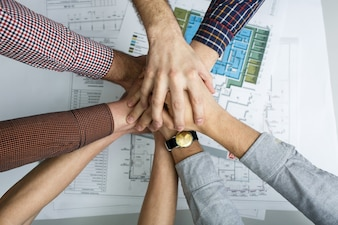 Colleagues standing with hands together