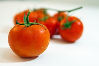 Collection of tomatoes with a light shadows, isolated on white,