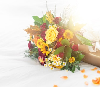 Colorful beautiful spring or summer bouquet of flowers on bed with golden gift box, holiday or surprise concept