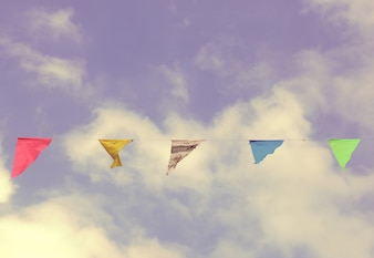 Colorful bunting flags on blue sky with pastel color style