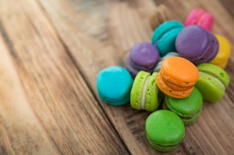 Colorful cookies with filling over stacked wooden table