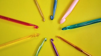 Colorful Crochet Hooks on Yellow Background