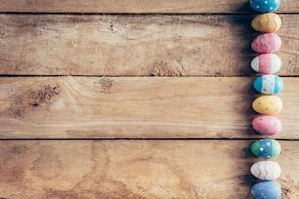 スペースで木製の背景にカラフルなパステルイースターエッグ。ヴィンテージトーン。