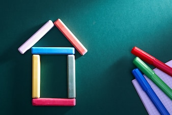 Colorful pieces of chalk put in form of house on blackboard