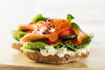 Colorful tasty salted salmon with vegetables on sandwich. Bright background.