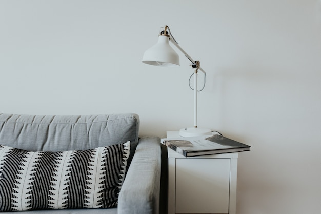 Comfortable couch in a modern house with a lamp on a little white shelf and a book with a waterfall