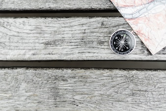Compass and map on a beautiful wooden surface. Top view