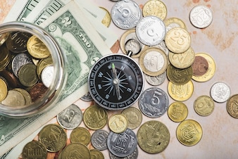 Compass with coins and banknotes