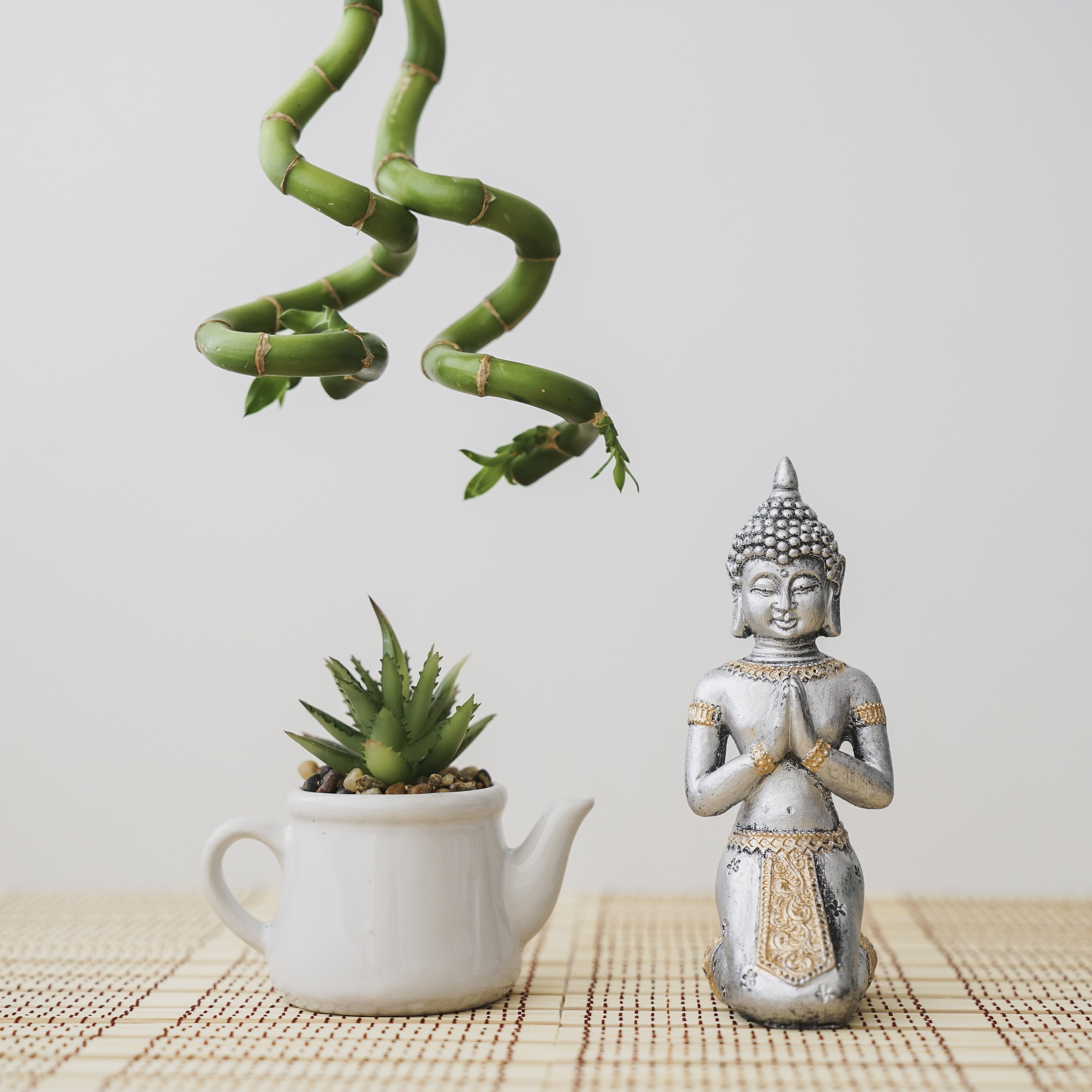 Composition of buddha and flowerpot with bamboo hanging