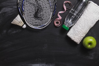 Composition with badminton racket, water bottle and apple