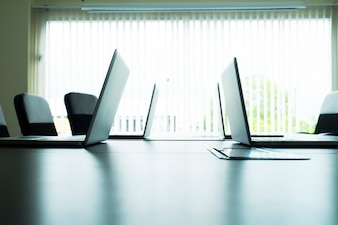 Computer laptops on table in meeting room.