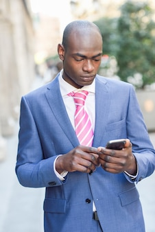 Concentrated businessman using his phone