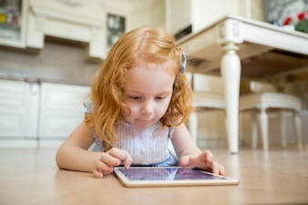 Concentrated little girl using touchpad on floor