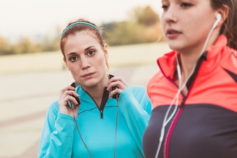 Concentrated sportswoman with hands on headphones