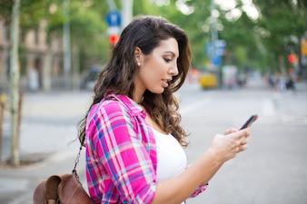 Концентрированный студент, используя смартфон на открытом воздухе