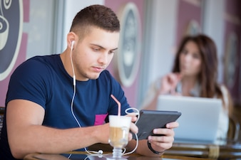 Concentrated teen listening to music with his tablet