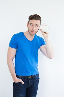 Concentrated young man eavesdropping with mug