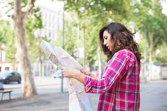 Concentrated young woman finding sight on map