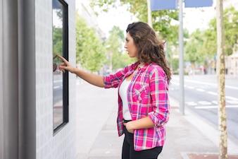 Концентрированная молодая женщина, касаясь цифрового экрана