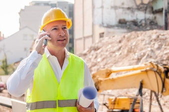 Confident architect. Handsome young man in hardhat holding blueprint and talking on the mobile phone while standing outdoors and against building structure