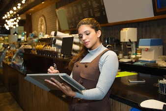 Confident cafe owner writing in register book