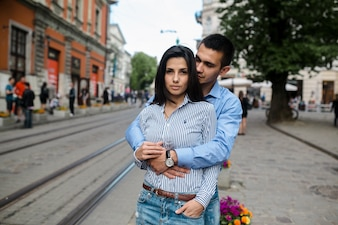 Confident couple embracing on street