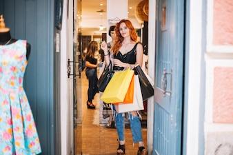 自信を持っている女性が店の出入り口でポーズをとる
