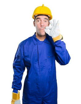 Confident workman keeping a secret on white background