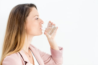 Confident young businesswoman drinking water