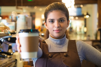 Confident young female coffee barista giving cup