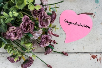 Congratulation note in heart shape paper with purple bouque