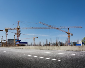 Construction site with cranes against blue sky