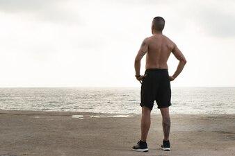 Созерцательный спортсмен без рубашки, наслаждающийся природой