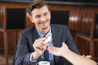 Content Businessman Giving Card to Waiter in Cafe