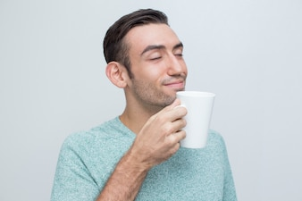 Content Handsome Young Man Smelling Tea From Mug