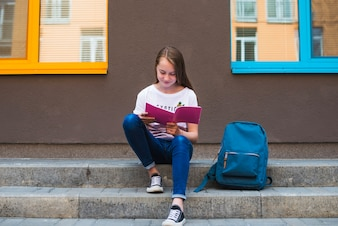 Content teen reading book on pavement