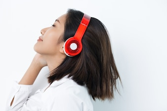 Content Woman in Headphones Listening to Music