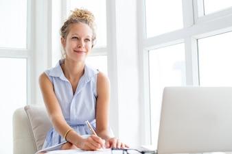 Контентная женщина, работающая с документами по лоджии