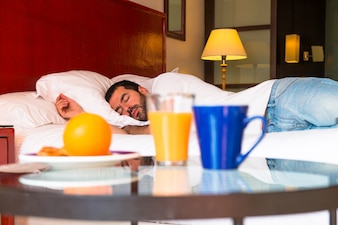 Continental breakfast and man sleeping in a hotel
