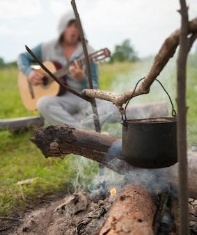 野火のキャンプで大釜で新鮮な食べ物を調理する