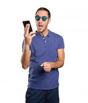 Cool young man using a mobile phone on white background