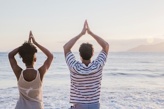 Couple doing yoga exercise at the beach